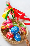 Traditional Czech easter decoration. Regional whip with ribbons with tulip and decorated red eggs in the wicker scuttle. Spring easter holiday arrangement Stock Photo