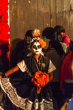 Traditional Day of the Dead Costume. A woman in a traditional Mexican dress carries flowers as part of her costume in Day of the Dead celebrations in Oaxaca royalty free stock photo