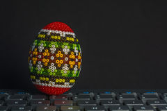 Traditional decorated Eastern egg over computer keyboard isolated on black Royalty Free Stock Photos