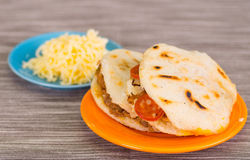 Traditional delicious arepas, shredded chicken avocado and cheddar cheese and shredded beef with grated cheese on wooden