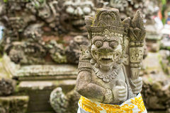 Traditional demon guard statue carved in stone in Bali island Stock Photos