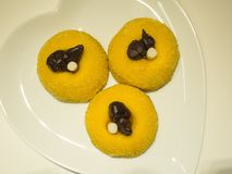 Traditional dessert of Bergamo: sweetened polenta and chocolate birds. Traditional dessert of Bergamo Italy: sweetened polenta and chocolate birds on yellow Stock Photo