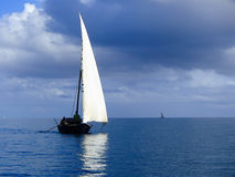 Traditional dhow sailing on a calm sea. Traditional dhow with white sail, sailing on calm blue seas with cloudy skies Royalty Free Stock Images