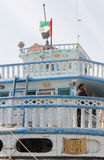 Traditional dhow transport boat flying the dubai flag at dubai creek, uae Stock Images