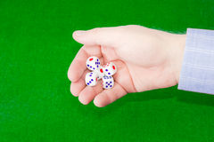 Traditional dice in male hand over table with green cloth Royalty Free Stock Photos