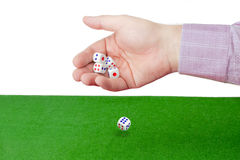 Traditional dice in male hand over table with green cloth Royalty Free Stock Photo