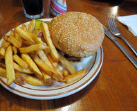 Traditional Diner Burger. The classic hamburger on a sesame seed bun, served with French fries, at the diner Royalty Free Stock Photo