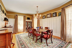 Traditional dining room interior with antique furniture and rug. Royalty Free Stock Photography