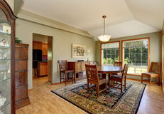 Traditional dining room interior with rug and big windows. Royalty Free Stock Images