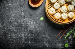 Traditional dish. Dumplings manta with meat in a bamboo steamer. On dark rustic background stock photography
