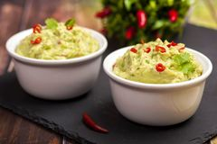 The traditional dish of Mexican cuisine. Guacamole. Avocado sauce with lime and chili. In a white bowl on a black portion board. Horizontal view royalty free stock images