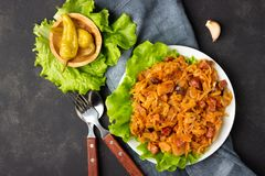 Traditional dish of polish cuisine - Bigos from fresh cabbage, meat and prunes. Top view. Dark background royalty free stock image