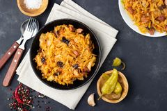 Traditional dish of polish cuisine - Bigos from fresh cabbage, meat and prunes. Top view. Dark background royalty free stock images