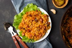 Traditional dish of polish cuisine - Bigos from fresh cabbage, meat and prunes. Top view. Dark background stock photography
