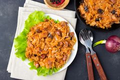 Traditional dish of polish cuisine - Bigos from fresh cabbage, meat and prunes. Top view. Dark background royalty free stock photo