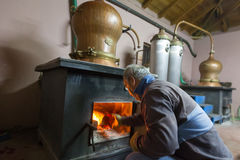 Traditional distillation of alcohol and production of homemade t. DRAMA, GREECE - NOVEBPER 15,2014: A man during the traditional distillation of alcohol and Royalty Free Stock Photos