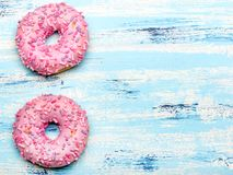 Traditional donuts on blue wooden background. Tasty doughnuts with icing, copy space Stock Images