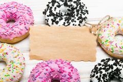 Traditional donuts and paper card on wooden background. Tasty doughnuts with icing, copy space Royalty Free Stock Images