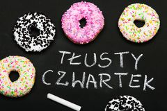 Traditional donuts with Polish words  Fat Thursday. Tasty doughnuts with icing Stock Photography