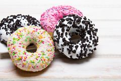 Traditional donuts on white wooden background. Tasty doughnuts with icing, copy space Stock Photo