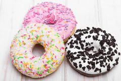 Traditional donuts on white wooden background. Tasty doughnuts with icing, copy space Royalty Free Stock Images