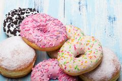 Traditional donuts on white wooden background. Tasty doughnuts with icing and powdered sugar, copy space Stock Image