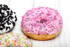 Traditional donuts on white wooden background. Tasty doughnuts with icing, copy space Royalty Free Stock Photography