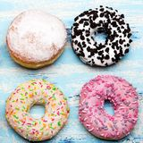 Traditional donuts on wooden background. Tasty doughnuts with icing and powdered sugar, copy space Stock Photography