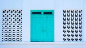Traditional Door flanked by pattern windows. Old, antique turquoise door flanked by full-size arabic pattern windows - Muscat, Oman Stock Photography