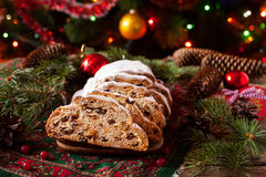 Traditional Dresdner German Christmas cake Stollen with raising, berries and nuts. Celebration decorations. Royalty Free Stock Image