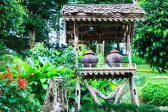 Traditional drinking water earthenware container under wooden shade shelter in green tropical ornamental garden in natural park ba. Ckground. Exterior Outdoor stock images