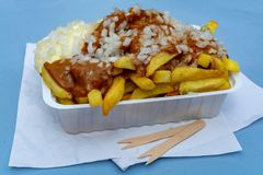 Traditional Dutch fast food dish, fried potatoes with sate sauce, onion and mayonaise, fat and not healthy street food. Close up royalty free stock photos