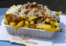 Traditional Dutch fast food dish, fried potatoes with sate sauce, onion and mayonaise, fat and not healthy street food. Close up royalty free stock photography