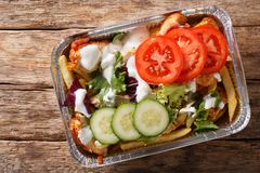 Traditional Dutch fast food kapsalon of french fries, chicken, f. Resh salad and sauce close-up on the table. Horizontal top view from above royalty free stock images