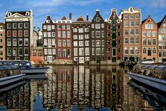 Traditional dutch medieval buildings in along the canal side,  reflected in water. Sunny day. Amsterdam, Netherlands. Stock Photography