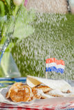 Traditional Dutch poffertjes. Small Dutch pancakes served with butter, suger and a Dutch flag. Poffertjes getting flavored by suger Royalty Free Stock Photos