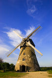Traditional dutch windmill in. Traditional Old dutch windmill in Latvia against blue sky with white clouds Stock Photography