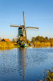 Traditional Dutch windmill at the bank of a canal Stock Image
