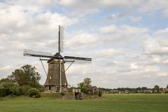 Traditional dutch windmill in the countryside in the Netherlands surrounded by pasture under a cloudy sky. stock photography