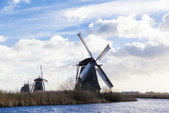 Traditional dutch windmill near the canal. Netherlands. Old windmill stands on the banks of the canal, and water pumps. White clou Royalty Free Stock Photos
