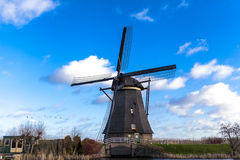 Traditional dutch windmill near the canal. Netherlands. Old windmill stands on the banks of the canal, and water pumps. White clou Royalty Free Stock Photo