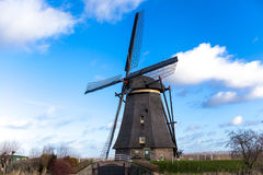 Traditional dutch windmill near the canal. Netherlands. Old windmill stands on the banks of the canal, and water pumps. White clou Royalty Free Stock Photography