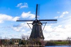 Traditional dutch windmill near the canal. Netherlands. Old windmill stands on the banks of the canal, and water pumps. White clou Royalty Free Stock Image