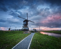 Traditional dutch windmills near water canals with cloudy sky, landscape Royalty Free Stock Photos