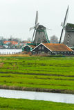 Traditional Dutch windmills and old farm house on river bank Stock Images