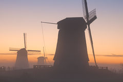 Traditional Dutch windmills in winter at sunrise royalty free stock photography