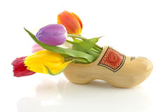 Traditional Dutch wooden shoe with tulips. Traditional yellow wooden shoe with colorful tulips isolated on white background Royalty Free Stock Photography