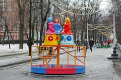 Traditional Dymkovo toy three women in headscarves as art object and Children`s carousel at Russian national festival `Shrove` in Stock Image