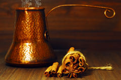 Traditional east coffee pot and spices on the table. Copper coffee pot in turkish style with fresh coffee with cinnamon and anise Stock Image