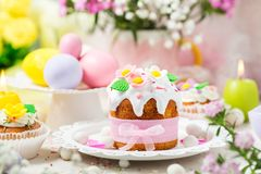 Traditional Easter cake and colorful eggs. Easter bread with white icing decorated sugar flowers and colorful eggs royalty free stock photos